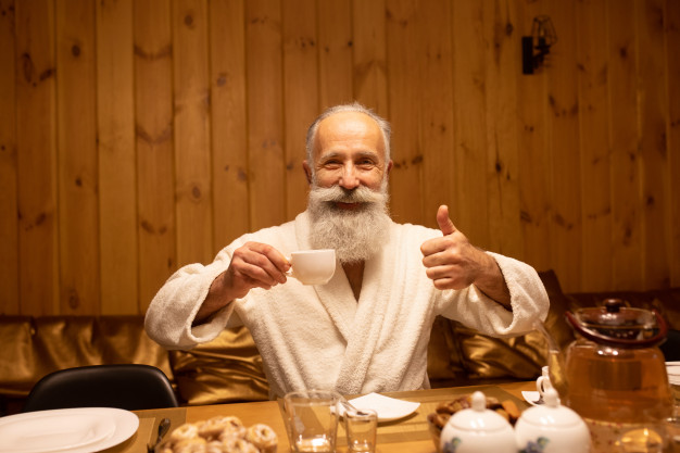 bearded-senior-man-drink-tea-after-the-procedure-in-the-sauna-concept-healthy-lifestyle_137441-429